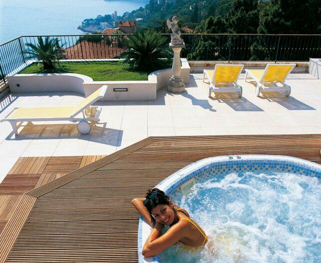 A l'extérieur, le spa Mosaïque Octavia valorise une terrasse en bois et permet de profiter de la vue en se relaxant.