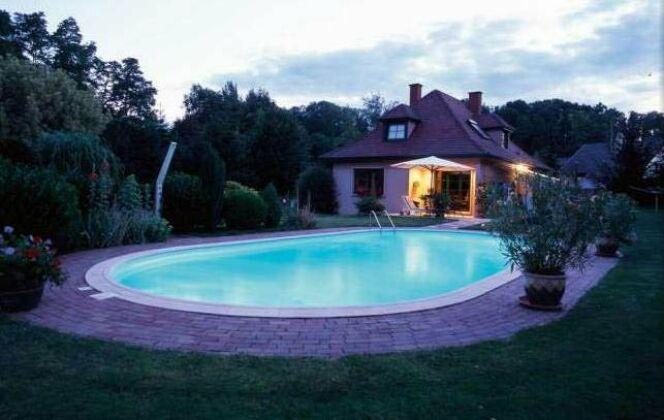 A la tombée de la nuit, l'éclairage de la piscine ovale Olivia sublime le jardin. Les pavés suivent les rondeurs de la piscine. © Waterair