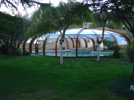 "Abris de piscine haut rotonde en bois Sun Abris<span class=""normal italic petit"">© Sun Abris</span>"