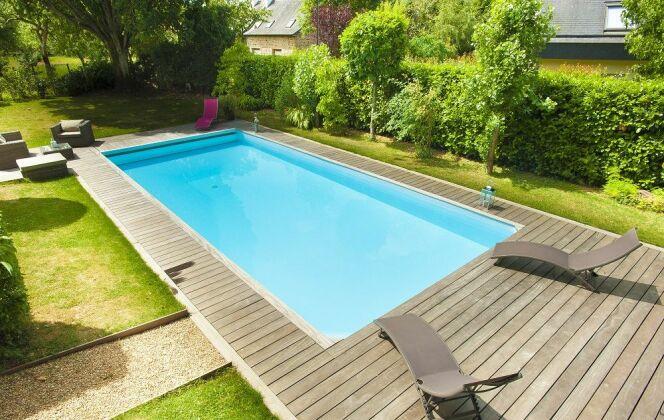piscine rectangulaire rénovée terrasse bois jardin pelouse © swimpool