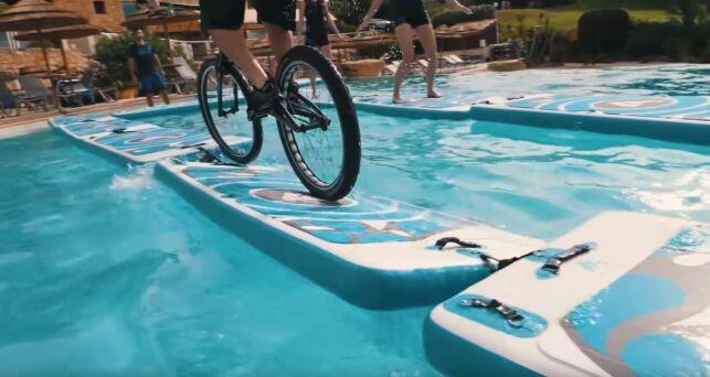 Aurélien Fontenoy traverse la piscine d'un hôtel en vélo sur des tapis Aquafitmat