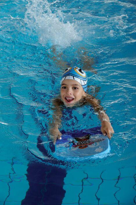 """Avec sa planche de natation et son bonnet de bain rigolo, l'enfant est paré pour la piscine !<span class=""""normal italic petit"""">© Arena</span>"""