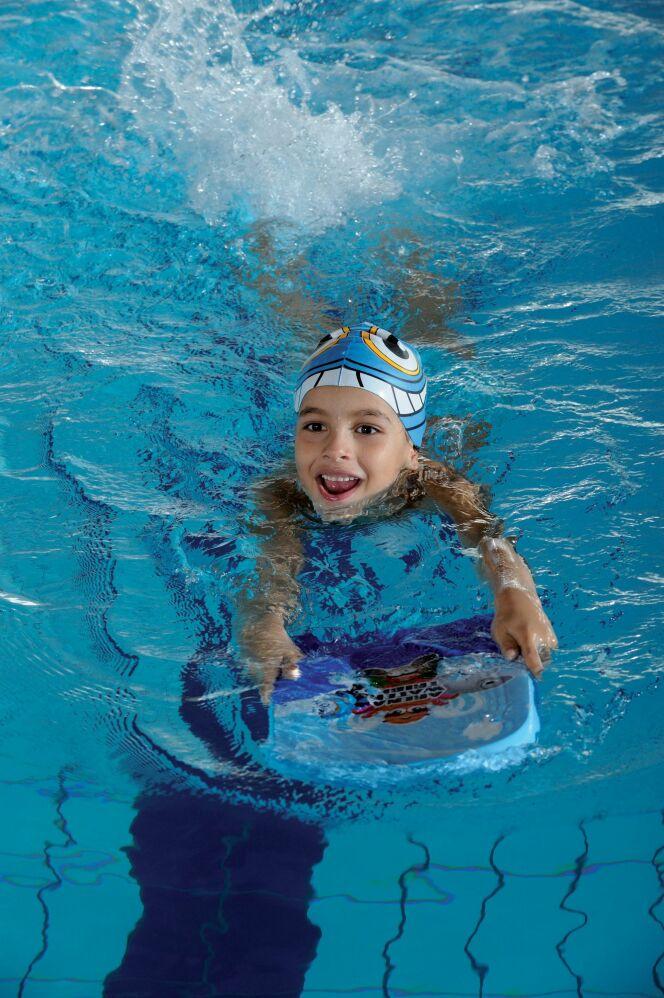 Avec sa planche de natation et son bonnet de bain rigolo, l'enfant est paré pour la piscine !
