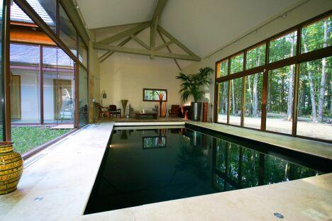 """Baie vitrée, liner noir et vue sur forêt : la piscine design entre mystère et  clarté<span class=""""normal italic petit"""">© L'Esprit Piscine</span>"""