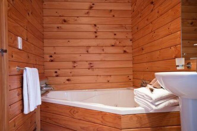 Baignoire balnéo asymétrique dans un chalet cosy en montagne. La baignoire asymétrique est idéale pour les petits espaces qu'elle mettra en valeur.