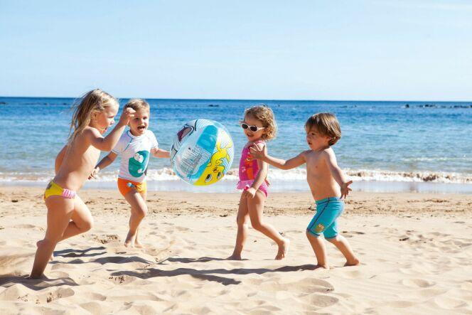 Bien protégés du soleil et équipés pour les premières brasses, les enfants peuvent s'amuser sur la plage.
