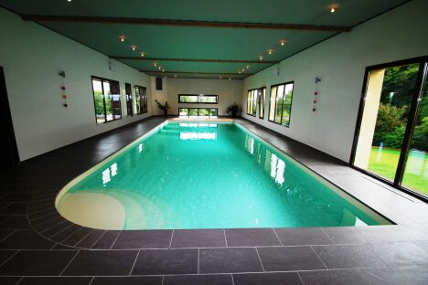 """Couloir de nage intérieur avec escalier d'angle arrondi et plages de carrelage noir<span class=""""normal italic petit"""">© L'Esprit Piscine</span>"""