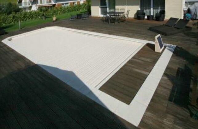 La couverture de piscine immergée, ici de la marque Abriblue, permet de protéger votre piscine de façon élégante.