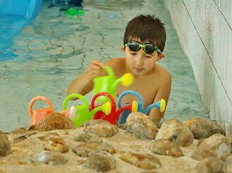 Enfant avec arrosoir à la piscine Nautil'ys au Crozon