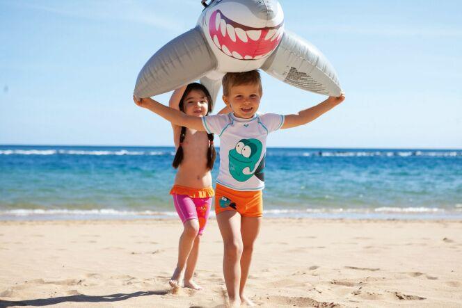 Enfants et requin gonflable sur la plage