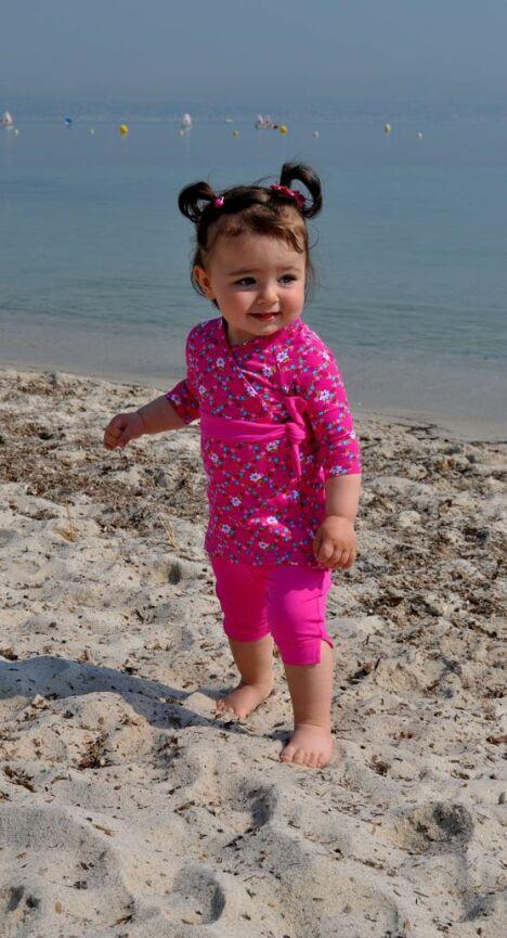 """Ensemble plage anti-UV fille manches longues et pantacourt rose à fleurs<span class=""""normal italic petit"""">© Little Duck</span>"""