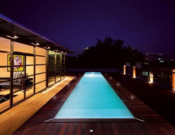 Entouré de bois, le couloir de nage par Piscinelle illumine les décors nocturnes