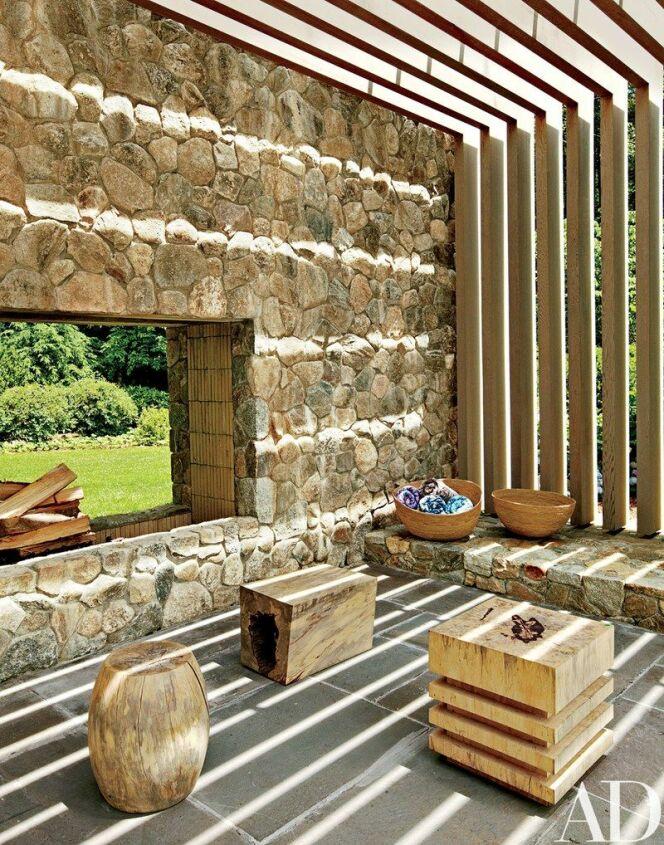 """L'intérieur du pool house, côté cheminée de bois.<span class=""""normal italic petit"""">© Architectural Digest</span>"""
