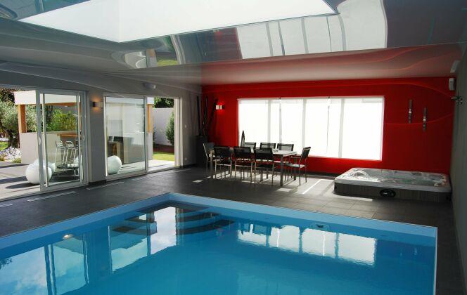 La piscine design intérieure fait partie du salon © L'Esprit Piscine