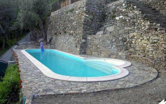 La piscine ovale Olivia se marie parfaitement avec les matériaux bruts comme la vieille pierre.