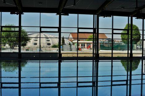 Le bassin sportif du centre aquatique d'Ottmarsheim donne une vue sur l'ancienne piscine Tournesol.