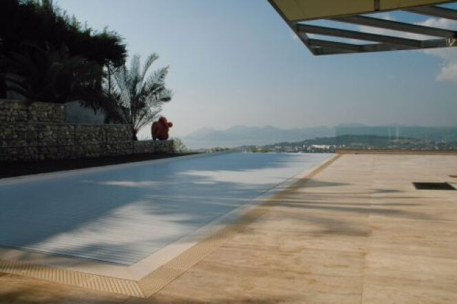 """Le rideau de piscine se déploie juste au ras de l'eau pour une protection en toute discrétion.<span class=""""normal italic petit"""">© Abriblue</span>"""
