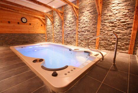 Le spa de nage Acrylique modèle Aquasport s'envisage à l'intérieur, agrémenté de pierres et de bois pour une ambiance chaleureuse