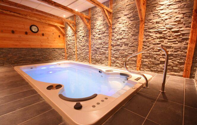 Le spa de nage Acrylique modèle Aquasport s'envisage à l'intérieur, agrémenté de pierres et de bois pour une ambiance chaleureuse © Clair Azur Spas