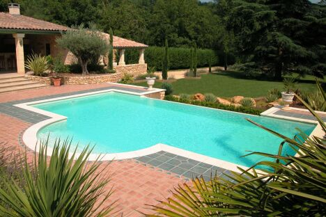 """Maison provençale avec piscine à débordement et escalier arrondi <span class=""""normal italic petit"""">© L'Esprit Piscine</span>"""