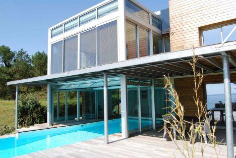 """Mélange de bois, verre et acier pour un décor moderne autour de ce couloir de nage in and out<span class=""""normal italic petit"""">© L'Esprit Piscine</span>"""