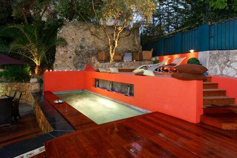Mélange des matériaux bruits et couleurs chaudes autour d'une piscine design savamment éclairée