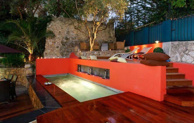 Mélange des matériaux bruits et couleurs chaudes autour d'une piscine design savamment éclairée © L'Esprit Piscine
