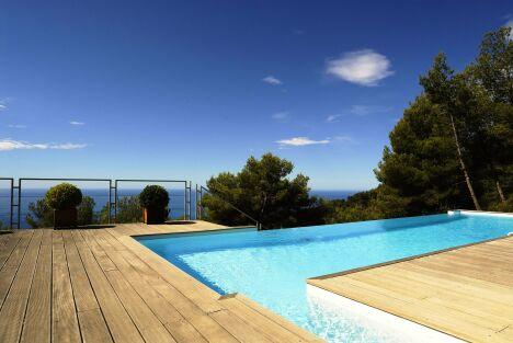 Piscine à débordement avec vue sur mer et solarium en bois