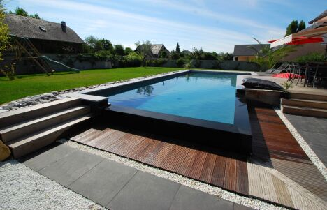 """Piscine à débordement design avec bordure noire et terrasse en bois<span class=""""normal italic petit"""">© L'Esprit Piscine</span>"""