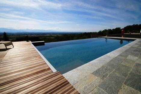 """Piscine à débordement entre pierre et bois, avec vue sur vallée<span class=""""normal italic petit"""">© L'Esprit Piscine</span>"""