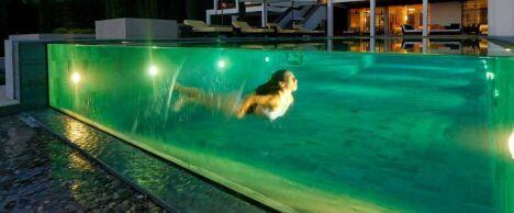 """Piscine à débordement sur paroi de verre, éclairée de nuit<span class=""""normal italic petit"""">© L'Esprit Piscine</span>"""