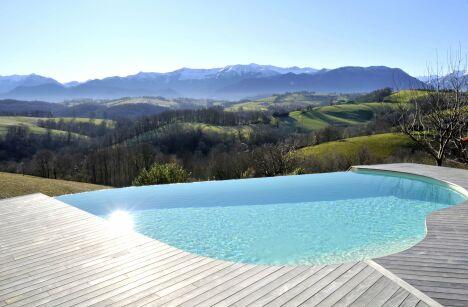 """Piscine en courbes à débordement sur vallée montagneuse<span class=""""normal italic petit"""">© L'Esprit Piscine</span>"""