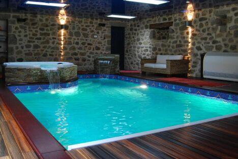 """Piscine et spa installés dans un cadre sublime et chaleureux avec mur en pierre et sol en bois<span class=""""normal italic petit"""">© L'Esprit piscine</span>"""