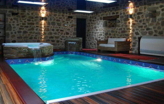 Piscine et spa installés dans un cadre sublime et chaleureux avec mur en pierre et sol en bois © L'Esprit piscine
