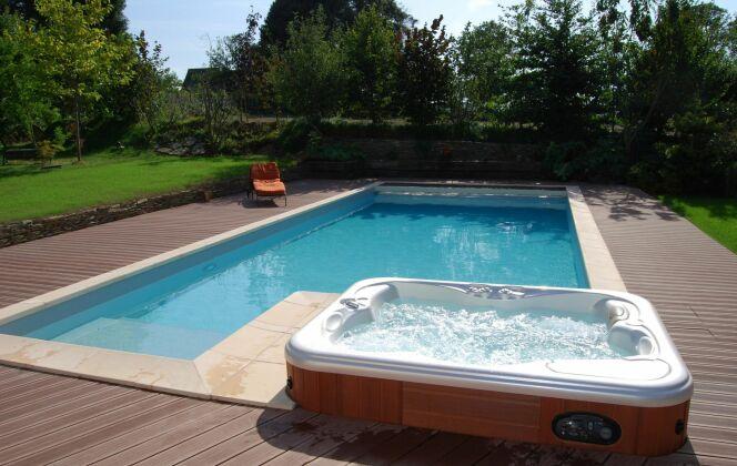 Piscine extérieure accompagnée de son spa pour de moments de détente et de bien-être © L'Esprit piscine