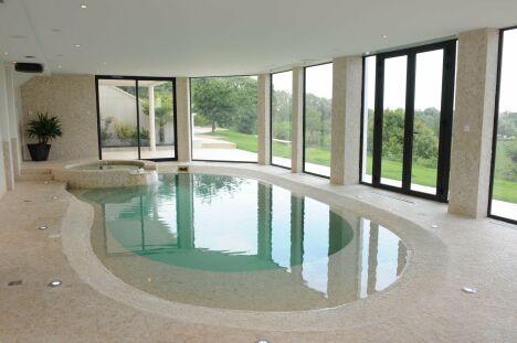 """Piscine intérieure avec plage immergée et spa, pour être en vacances chez soi toute l'année.<span class=""""normal italic petit"""">© Diffazur</span>"""