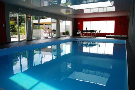 """Piscine intérieure avec spa et plafond miroir, vue sur terrasse<span class=""""normal italic petit"""">© L'Esprit Piscine</span>"""