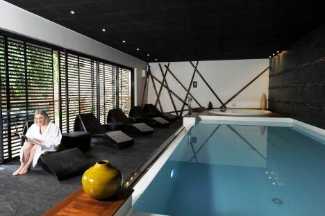"""Piscine intérieure contemporaine avec plafond noir, spa et transats<span class=""""normal italic petit"""">© L'Esprit Piscine</span>"""