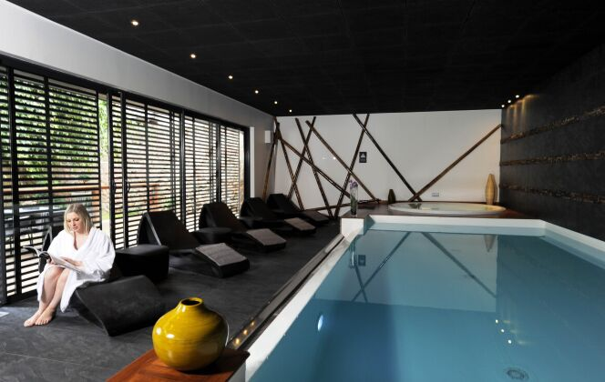 Piscine intérieure contemporaine avec plafond noir, spa et transats © L'Esprit Piscine