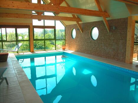 Piscine intérieure entourée de carrelage et murs de pierre claire, poutres de bois et vue sur verdure