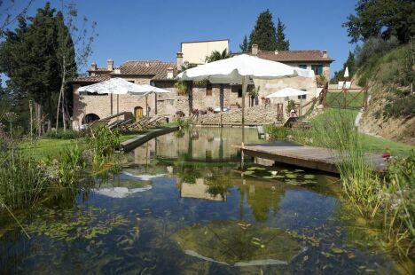 """Piscine naturelle et maison en pierres<span class=""""normal italic petit"""">© Living-Pool de BIOTOP - www.baignade-ecologique.com</span>"""
