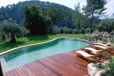 Piscine à débordement avec solarium en bois lustré et vue sur montagne