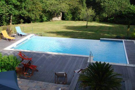 """Piscine à débordement sur pelouse avec solarium en bois<span class=""""normal italic petit"""">© L'Esprit Piscine</span>"""