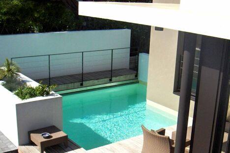 Piscine design conçue autour d'un angle de maison pour optimiser l'espace