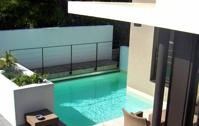 Piscine design conçue autour d'un angle de maison pour optimiser l'espace © L'Esprit Piscine