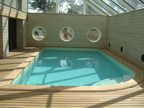 """Piscine intérieure avec escalier d'angle arrondi, plages de bois clair et fenêtres hublots<span class=""""normal italic petit"""">© L'Esprit Piscine</span>"""