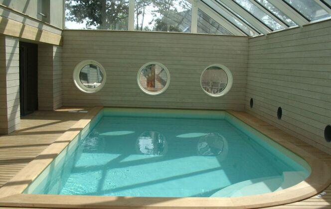 Piscine intérieure avec escalier d'angle arrondi, plages de bois clair et fenêtres hublots © L'Esprit Piscine