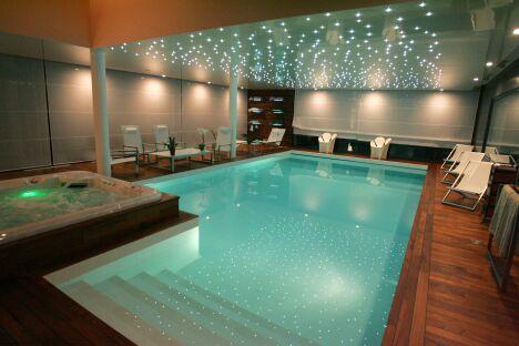 Piscine intérieure avec jacuzzi, plages de parquet en bois lustré et plafond étoilé de LED