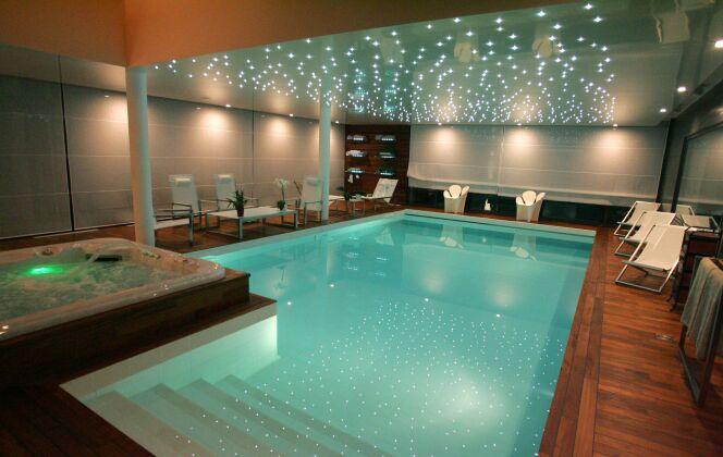 Piscine intérieure avec jacuzzi, plages de parquet en bois lustré et plafond étoilé de LED © L'Esprit Piscine