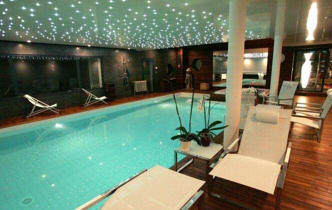 Piscine intérieure avec plafond étoilé de LED, plages de parquet en bois et miroir © L'Esprit Piscine